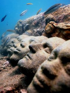 many different faces sculpted underwater on one rock together...