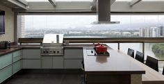 O projeto do arquiteto Léo Shetman foi concebido buscando o conforto da família. O gourmet tem seu balcão revestido com pastilhas nude e madeira escura integrada à bancada em carvalho claro. Eletrodomésticos e uma moderna churrasqueira em aço inox ocupam o espaço.