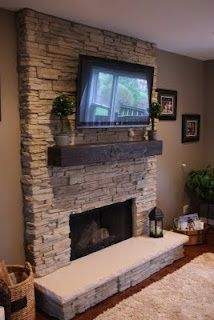 Stacked stone fireplace with reclaimed wood mantel.