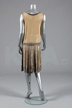 Beaded and sequined dress - French c. 1928  The pale apricot muslin base is spangled overall with clear glass seed beads. Black, gold and pearlescent beads and sequins are used in patterns on the bodice and scalloped skirt Back 2 Private collection