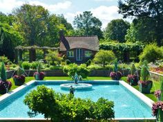 Decor – Pools :     On closer inspection you will notice the adorable English Cottage, pool house at the far end of the pool. You can also see the amazing statuary placed amidst the pool fountains.   Large square painted wood planters frame out the pool with evergreens and trailing vines,... - #Pool