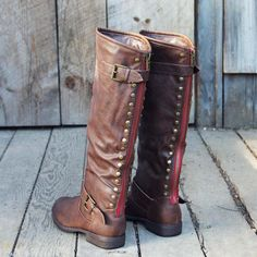 "Rich chestnut tones adorn these darling zipper & studded detail riding boots. Antiqued brass hardware pairs with a sweet rust red back zipper, stud & buckle details, and a soft inner lining. Stacked heel. The perfect boot for chilly fall and winter weather. Color: Chestnut Brown Heel Height: 1"" Boot Height: 16"""
