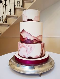 Wedding cake for rock climbers. Hand painted wedding cake with mountains accented with edible gold leaf. Burgundy marble effect top and bottom tier with icing ropes and climbing knots.