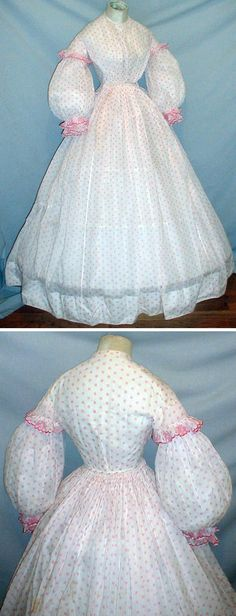 Summer day dress, ca. 1860s. Lightweight cotton with pink dotted pattern on white background. Bell-shaped sleeves have short caps. Oversleeve and cuffs trimmed with printed ruffles. Neck, armscyes, and waist are piped. Bodice lined with cotton; it has front hook and eye closure. Skirt attached to waist with cartridge pleating and is unlined. fiddybee/ebay