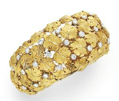 A DIAMOND AND GOLD CUFF BRACELET, BY BUCCELLATI   The hinged cuff designed as a sculpted 18k gold foliate cluster, interspersed with circular-cut diamonds, mounted in 18k gold, 2 1/8 ins. diameter, in a Buccellati navy satin box  Signed Buccellati, Italy