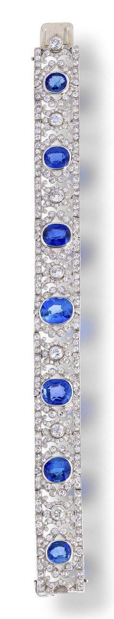 An art deco sapphire and diamond bracelet, French, circa 1925  designed as seven oval and cushion-cut sapphires within a flexible strap of scrolling foliate links set with old European and old single-cut diamonds, accentuated by scroll engraved edges; with French assay and maker's mark; estimated total sapphire weight: 21.00 carats; estimated total diamond weight: 8.90 carats; mounted in platinum; length: 7 1/8in.