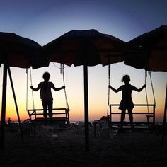Two girls play on swinging seats as the sun sets on Gaza Beach.  22 photos of kids just being kids