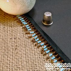 Beaded trim/fringe with seed beads of opaque milky turquoise blue, and semi sheer bronze brown arranged in stripes. Beads are attached to a black satin ribbon. The variety of beads gives a subtle shimmer to the trim. Beaded Trim, Fringe Trim, Haberdashery, Pearl Beads, Black Satin, Seed Beads, Lilac, Beaded Bracelets, Bronze