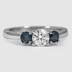 An elegant three stone trellis ring with two beautiful blue sapphires. jewelry, diamonds