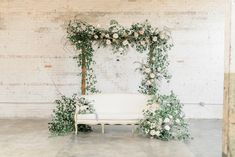 Simple rustic wooden arch dressed with an abundance of delicate foliage and soft blush roses teamed with a stunning French style sofa. What a statement!