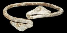 """VIKING SILVER BALTIC SNAKE BRACELET Circa 10th century AD or later  A silver bracelet of rectangular section, the finials formed as recurved serpentine heads with punched annular eyes and notched detailing. Silver, 15 grams, 57 mm (2 1/4"""")."""