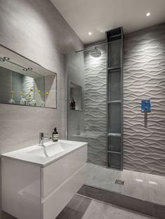 Bathroom Tile Idea - Install 3D Tiles To Add Texture To Your Bathroom   The wavy pattern of these shower tiles give the bathroom a serene feel and resembles the look of a rippling river or stream.
