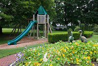 Kids backyard near garden, with tree house, sliding board, tiered plantings of petunias , trees, shade, swings, boxwood, lawn
