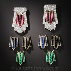 Fantastic four-in-one dress clips! The center sections are exchangeable in four delicious flavors: Cherry red rubies, lime green emeralds, minty blue sapphires and black licorice onyx. The classic Art Deco, architectural chevron motifs are crafted in platinum and packed with sparkling white full-cut diamonds. The colorful inserts are framed in 18K yellow gold and match the double pin backs. All eight pieces reside in their original fitted box along with two mini-screwdriver type tools…