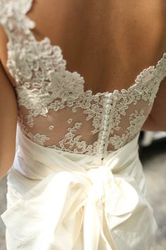 The back of your wedding gown can be just as stunning as the front.  Lace backs with satin covered buttons are very popular this year.