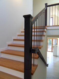 Klasyczne schody zabudowane z jasnym drewnem i białą podstopnicą.