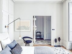 House tour: a modern French apartment within an opulent 19th-century shell: The eye-catching paper light seen through the doorway in the entry hall is Isamu Noguchi's 'Akari E' design, produced by Vitra.