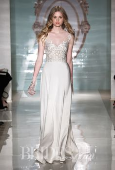 Brides.com: Reem Acra - Spring 2015. Silk crepe A-line wedding dress with an illusion tip-of-the-shoulder neckline and an embroidered bodice, Reem Acra