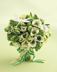 A sleek white dragonfly (we painted it white) perches atop verdant masses of green and white, giving this bouquet a fresh, summer-day feel. Dragonfly from Floraltrims. Two-inch cotton-striped ribbon (#2101, color #277) from Hyman Hendler and Sons, 212-840-8393.