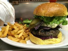 The John Tory burger: 6 oz ground chuck, fried red onions, blue cheese, and smoky-sweet blueberry BBQ sauce, topped with blue corn tortilla chips and all the fixin's! Blue Corn Tortilla Chips, Blue Cheese, Onions, Hamburger, Blueberry, Fries, Bbq, Ethnic Recipes, Barbecue