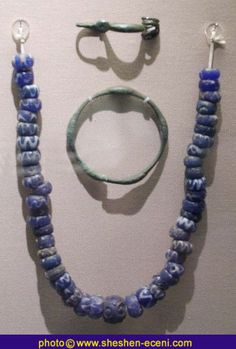 bronze brooch, bronze bangle, and blue glass bead necklace found in burials in the Arras cemetery, East Yorkshire.c. 400 - 100 BC (British Museum