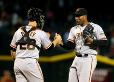 San Francisco Giants catcher Buster Posey (28) and Santiago Casilla celebrate after defeating the Arizona Diamondbacks 2-1 during a baseball game, Tuesday, Sept. 16, 2014, in Phoenix. (AP Photo/Rick Scuteri)