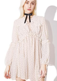 For Love & Lemons Creme Dot Truffles A-Line Dress will have you feelin' so sweet and sassy, babe. This beautiful long sleeve dress features ruffle details at the chest and waist, ties at the neck and sleeves, and a polka dot pattern all over.