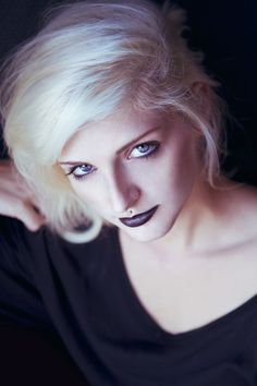 dark purple lipstick with black lip liner paired with minimal eye makeup, black mascara and matte face powder.