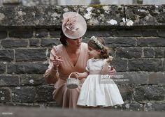 TOPSHOT - Britain's Catherine, Duchess of Cambridge (L) speaks to her daughter Britain's princess Charlotte, a bridesmaid, following the wedding of her sister Pippa Middleton to James Matthews at St Mark's Church in Englefield, west of London, on May 20, 2017. After turning heads at her sister Kate's wedding to Prince William, Pippa Middleton graduated from bridesmaid to bride on Saturday at a star-studded wedding in an English country church. The 33-year-old married financier James…