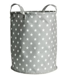Gray/stars. Cylindrical storage basket in thick polyester with a printed pattern. Two handles and concealed metal rim at top for stability. Plastic coating