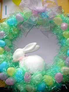 Easter Wreath made with Plastic Easter Eggs and Easter grass Hot glue gunned onto a paper wrapped metal wreath Ring