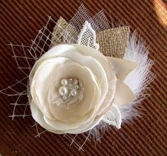 This rustic hair flower is hand made ​​of ivory satin and champagne chiffon, lace, burlap, beads, pearls, rhinestones, Swarovski crystals, french netting, tulle and white feathers. All petals are handcut and hand singed one-by-one. It is attached to an alligator clip with teeth.Awesome decoration for:Rustic WeddingCountry WeddingOutdoor WeddingFall WeddingCottage Chic WeddingFlower size is ~3