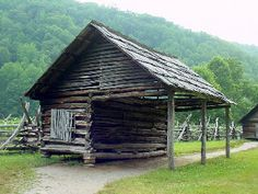 """corn crib and gear shed. The toolshed housed farm equipment like plows, harrows, cythes, hoes, and rakes. """"A wagon loaded with ears of dried corn was driven under the shed portion of this structure and the corn was tossed over the log wall into the crib."""" This corn crib most probably held corn for livestock due to its proximity to the barn and other livestock areas."""