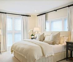 Good example of window behind bed with layered blinds and long drapes.