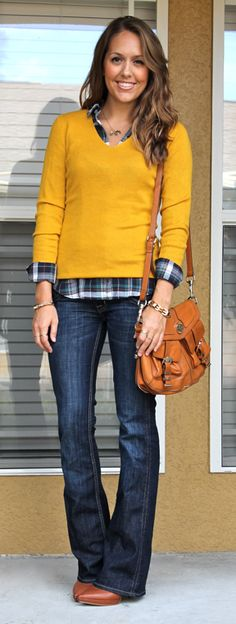 A mustard sweater is classic & polished layered over a plaid button up & paired with bootcut jeans.
