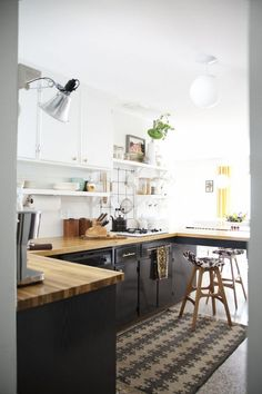 Colour palette - black lower cabinetry, white/glass uppers, and wooden benches
