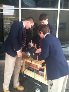 Robotics/Engineering students working on their project outside of the Sci/Tech Building.