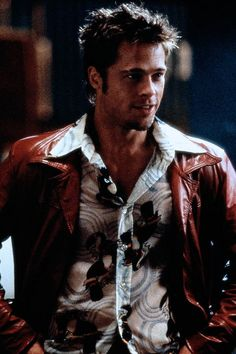 Tyler Durden had three distinctive looks in Fight Club:  thrift store grunge, morning time schulb, and whatever sorta fits works.  His classic 70s era red leather jacket with yoke detail, and floral shirts were his beginning look (and also my fav look).  He had his dingy bathrobe for his early mornings.  And then finally his array of tight fitting shirts that may or may not coordinate and have runs/holes in the them. Costume designer  Michael Kaplan did an amazing job with the wardrobe.