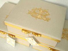 Caixa em madeira MDF, revestida em tecido cor linho - com brasão iniciais dos noivos bordado em dourado - com fita dourada.  A caixa tem 3 divisórias - para 1 garrafa de Baby Chandon e 2 divisórias para bem-casados ou gravata.  Pedido Mínimo: 15 unidades. R$ 37,30