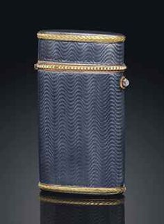 A GEM-SET, GOLD-MOUNTED SILVER-GILT AND GUILLOCHÉ ENAMEL CIGARETTE CASE BY FABERGÉ, WORKMASTER HENRIK WIGSTRÖM, ST PETERSBURG, 1908-1917. Étui-form, the body enamelled overall in translucent grey-blue over a wavy guilloché ground, with gold laurel borders, the hinged cover set with a seed-pearl border, with a cabochon moonstone push-piece.