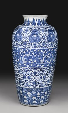 A BLUE AND WHITE 'SOLDIER' VASE QING DYNASTY, KANGXI PERIOD of tapering ovoid form with waisted neck and everted rim, finely painted with a central border of writhing chilong amidst lingzhi in reserve on a blue ground, between bands of stylized lotus with borders of upright leaves at the neck and stylized scrolling lotus as the foot, Height 36 1/2  in
