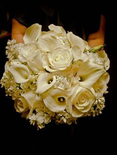 Flowers: The bridal bouquet will be a modern Modern clutch bouquet of ivory stock flowers, Picasso calla lilies, cream roses, and tufts of white feathers wrapped in ivory ribbon with the stems showing.
