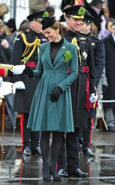 Celebrity Fashion: Kate Middleton wearing an Emilia Wickstead soft pleated coat dress she wore last year with a black high neck tunic, matching tights, and her go to black suede shoes. Kate, or Catherine, Duchess of Cambridge and Prince William, Duke of Cambridge attend a St Patrick's Day parade by the 1st Battalion Irish Guards as they visit Aldershot Barracks on St Patrick's Day on March 17, 2013 in Aldershot, England.