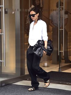 Wearing a white blouse, black trousers, and flat sandals and toting a leather satchel.                  Ima...