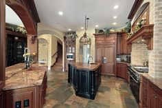 Cozy but large kitchen with dark-toned tile floor pattern, brick walls (on one side), dark island and wood cabinets capped with an order-lik...