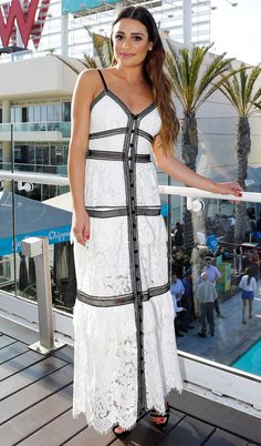 LEA MICHELE wearing a white maxi dress with black, lacy details and black sandals.