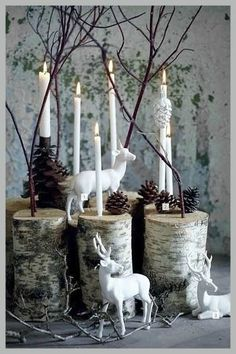 Nordic woodland Christmas scene with birch logs, pine cones and white deer figurines.