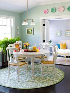 Circle Style:: A circle floor rug mirrors the shape of the table and creates a unified look in the nook separate from the rest of the kitchen. Using a shape motif is an easy way to add savvy style. Decorative plates continue the pattern above the doorway. Bright colors make this area a perfect space to start the day.