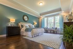 Luxury teal master bedroom with tray ceiling, wood floors and area rug