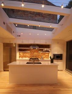 Кухня, в которой использована нейтральная цветовая гамма и оригинальные стеклянные панельные потолки, которые визуально расширяет пространство помещения.